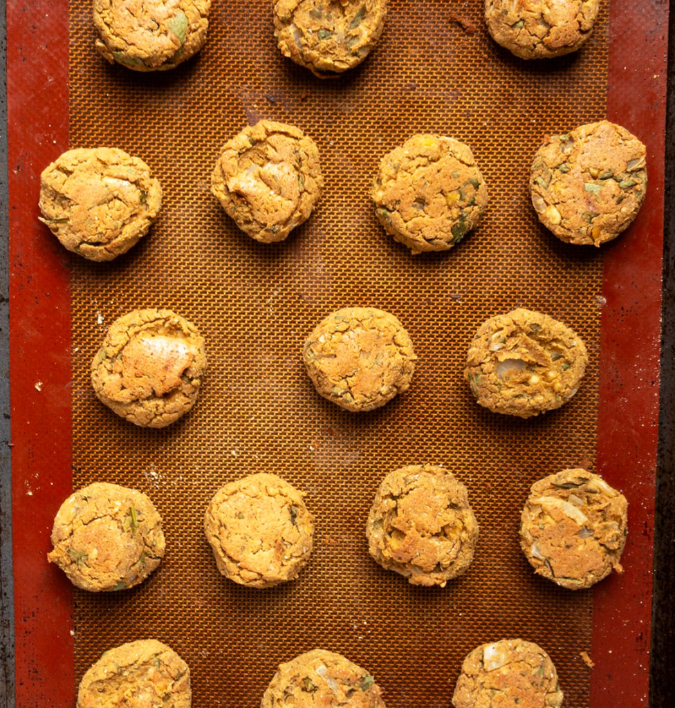 Baked falafel balls on a silicone mat lined baking tray