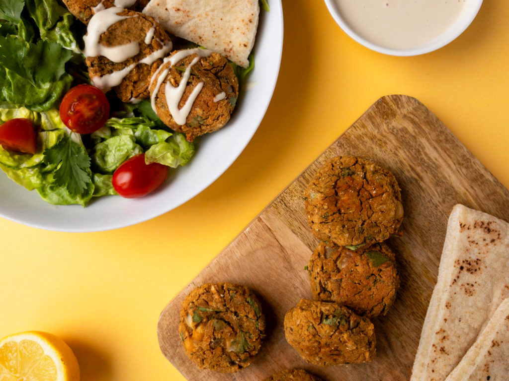 Lettuce, tomato, and falafel salad with simple tahini sauce. Extra falafel balls on the side with pita bread.