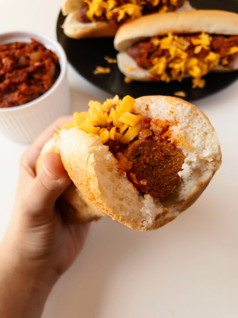Hand holding a vegan Chili Cheese Dog with a bite taken out of it.