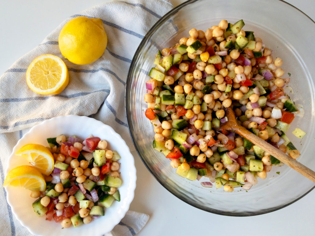 A large servings bowl of chickpea salad, with a smaller bowl of salad, and two lemons.