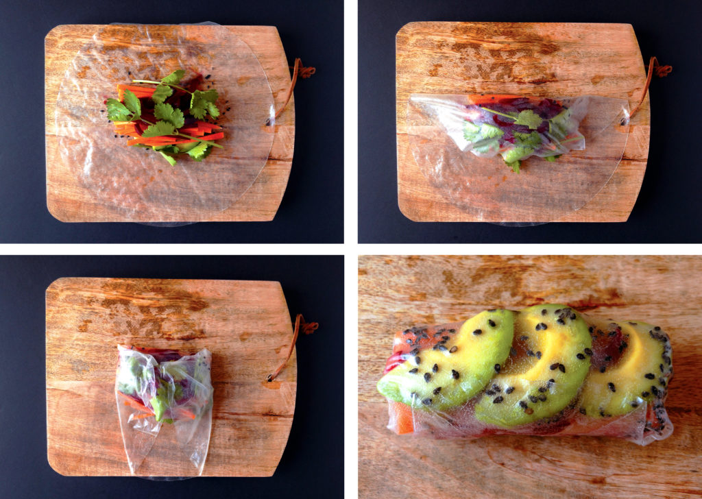 A wet Rice Paper wrap on a wooden cutting board with veggies packed in the center. Another rice paper wrap fully rolled.