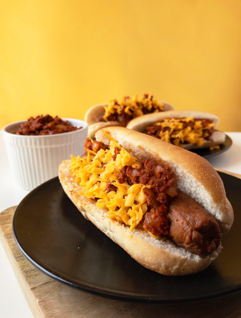 Three vegan Chili Cheese Dogs on plates and vegan chili sauce in a bowl.