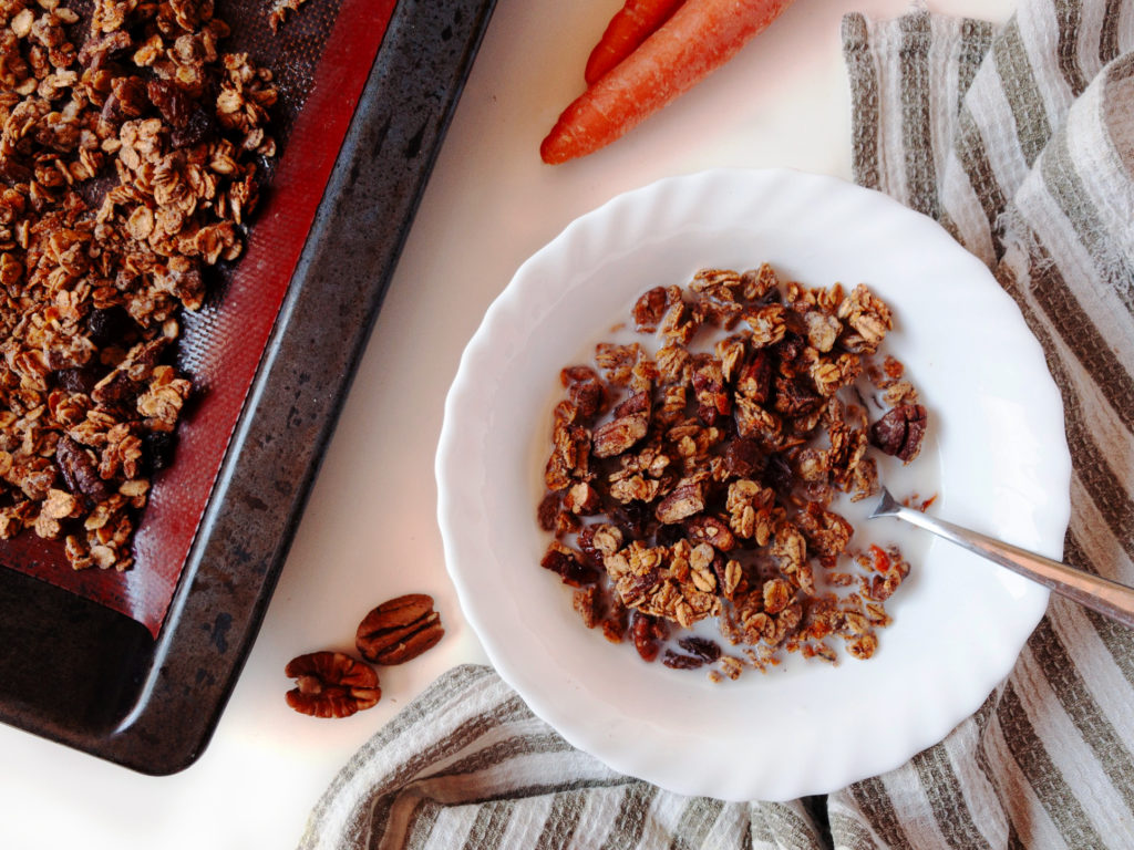 Small white bowl full of carrot cake granola and almond milk with a baking tray of cooked carrot cake granola