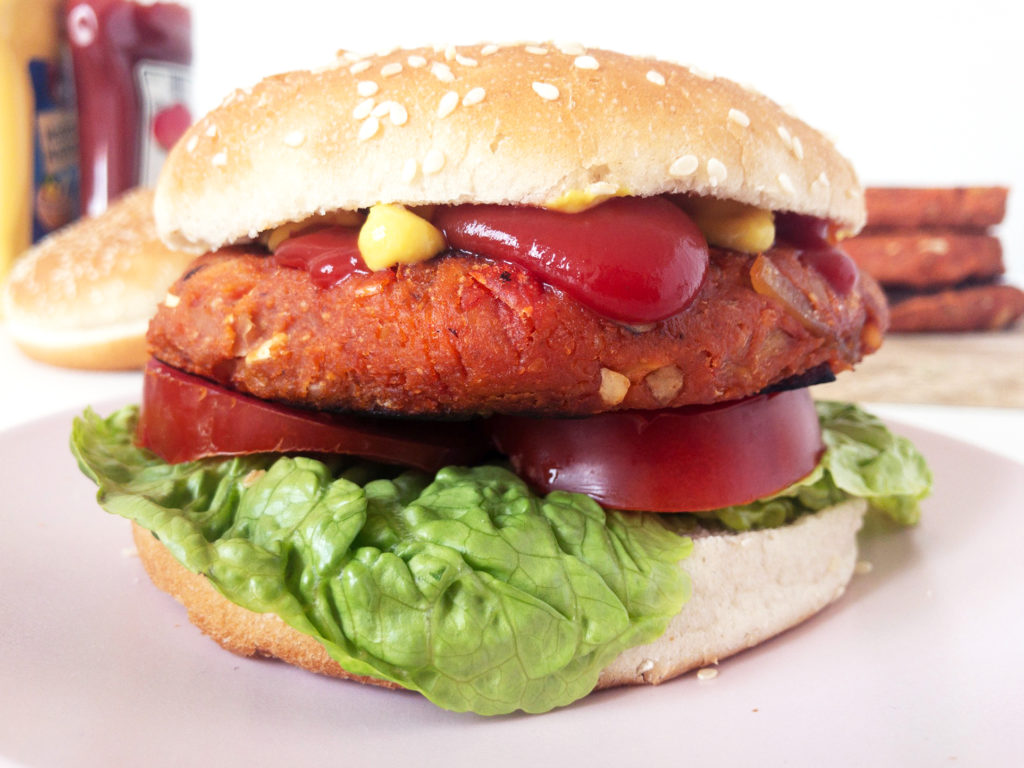 Classic chickpea veggie burger with a sesame seed bun, tomato, lettuce, and overflowing with mustard and ketchup.