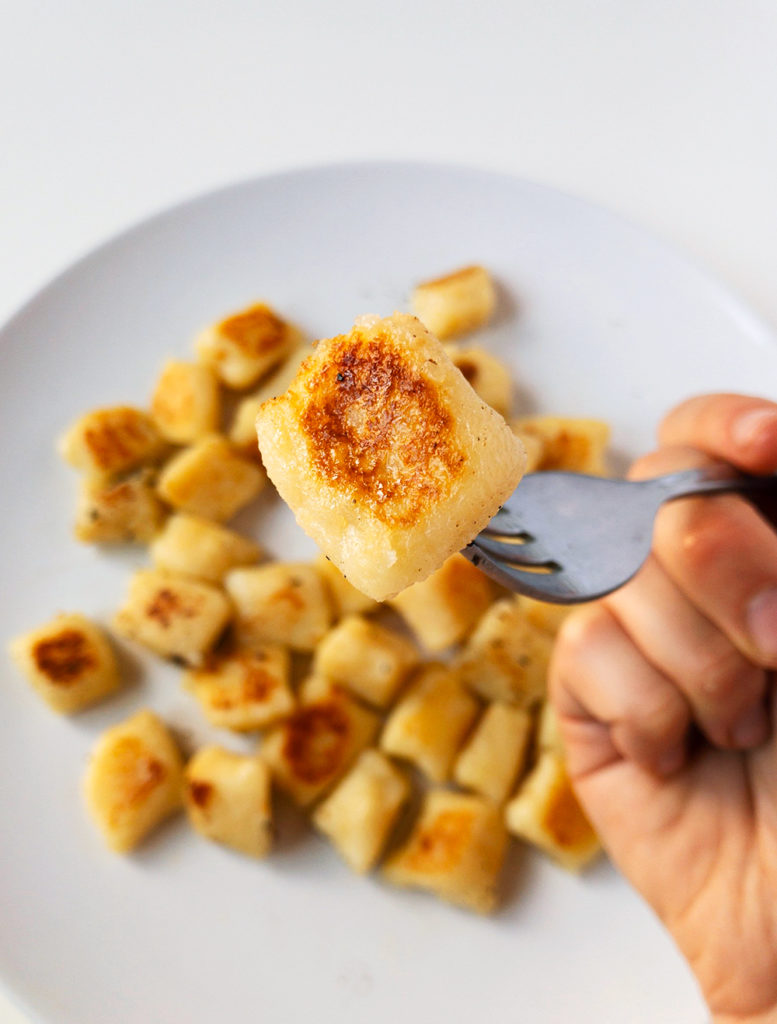 Cooked lightly golden gnocchi on a fork.