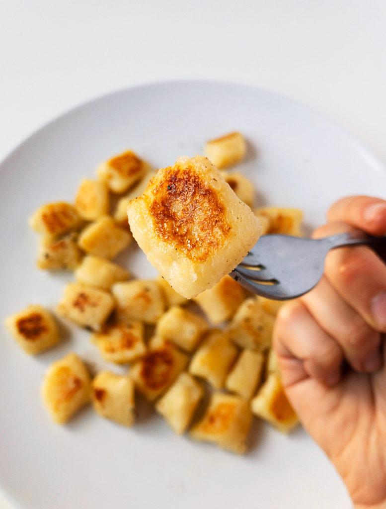 Cooked lightly golden gnocchi on a fork.