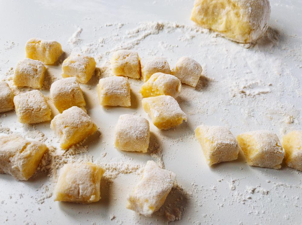 Uncooked, floured gnocchi dumplings on a white surface