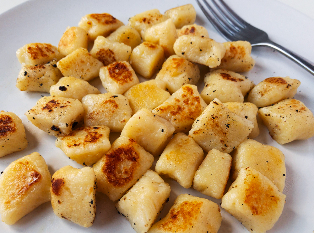 Lightly golden gnocchi dumplings on a white plate