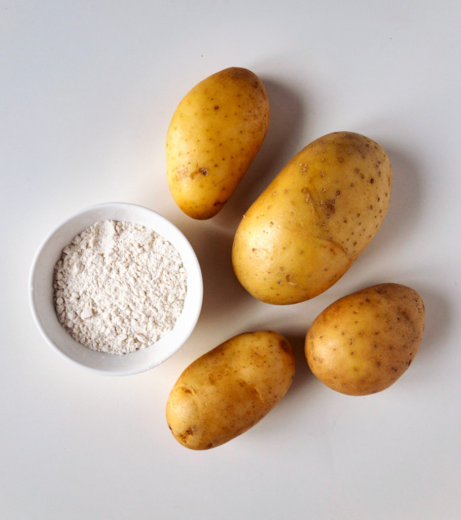 Four, small yellow potatoes and a small bowl of all purpose flour