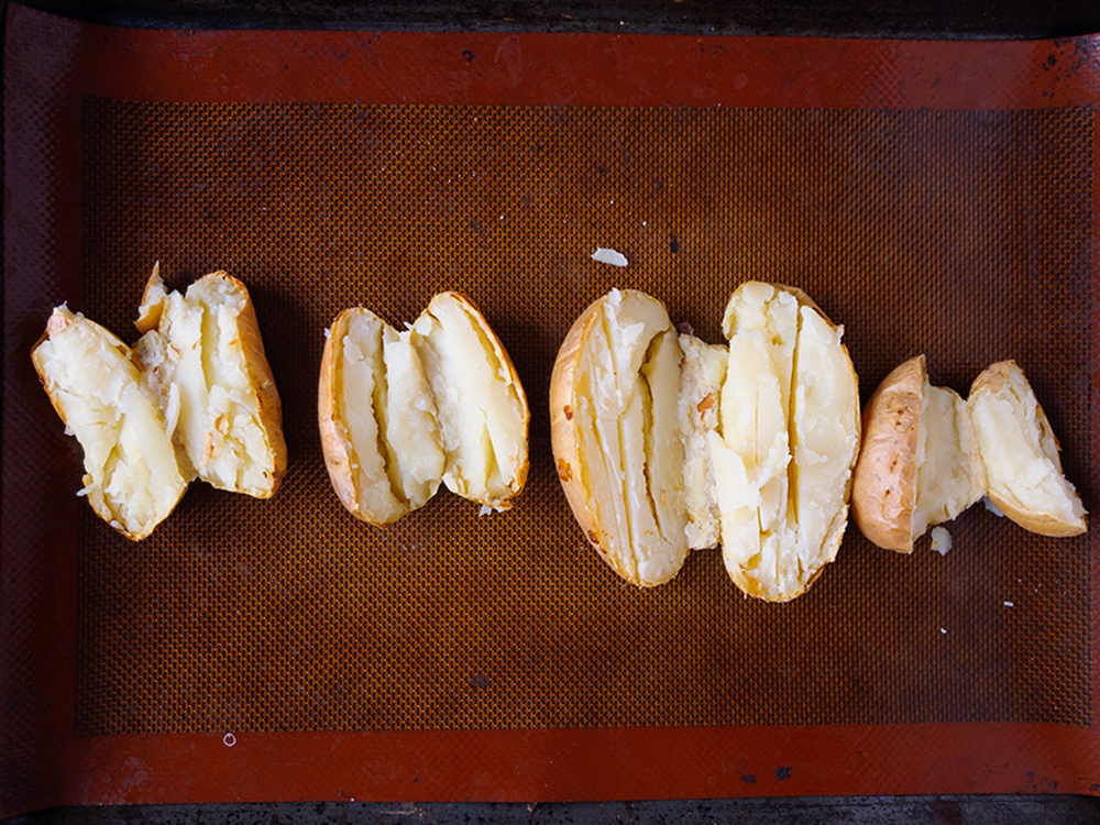 Four baked potatoes cut open on a baking tray