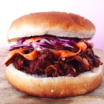 BBQ Jackfruit with Vegan Coleslaw in a burger bun on a wood cutting board