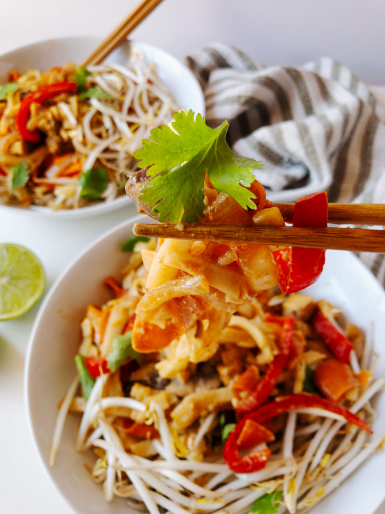 Chopsticks holding up a bite of easy vegan tahini pad thai topped with bean sprouts and cilantro.