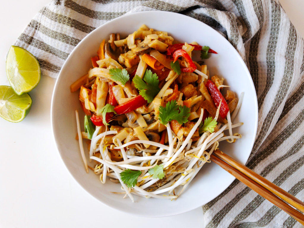 Bowl of easy Tahini Pad Thai with chop sticks and lime wedges.