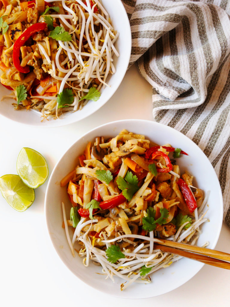 Bowl of easy vegan tahini pad thai topped with bean sprouts and cilantro with chopsticks.