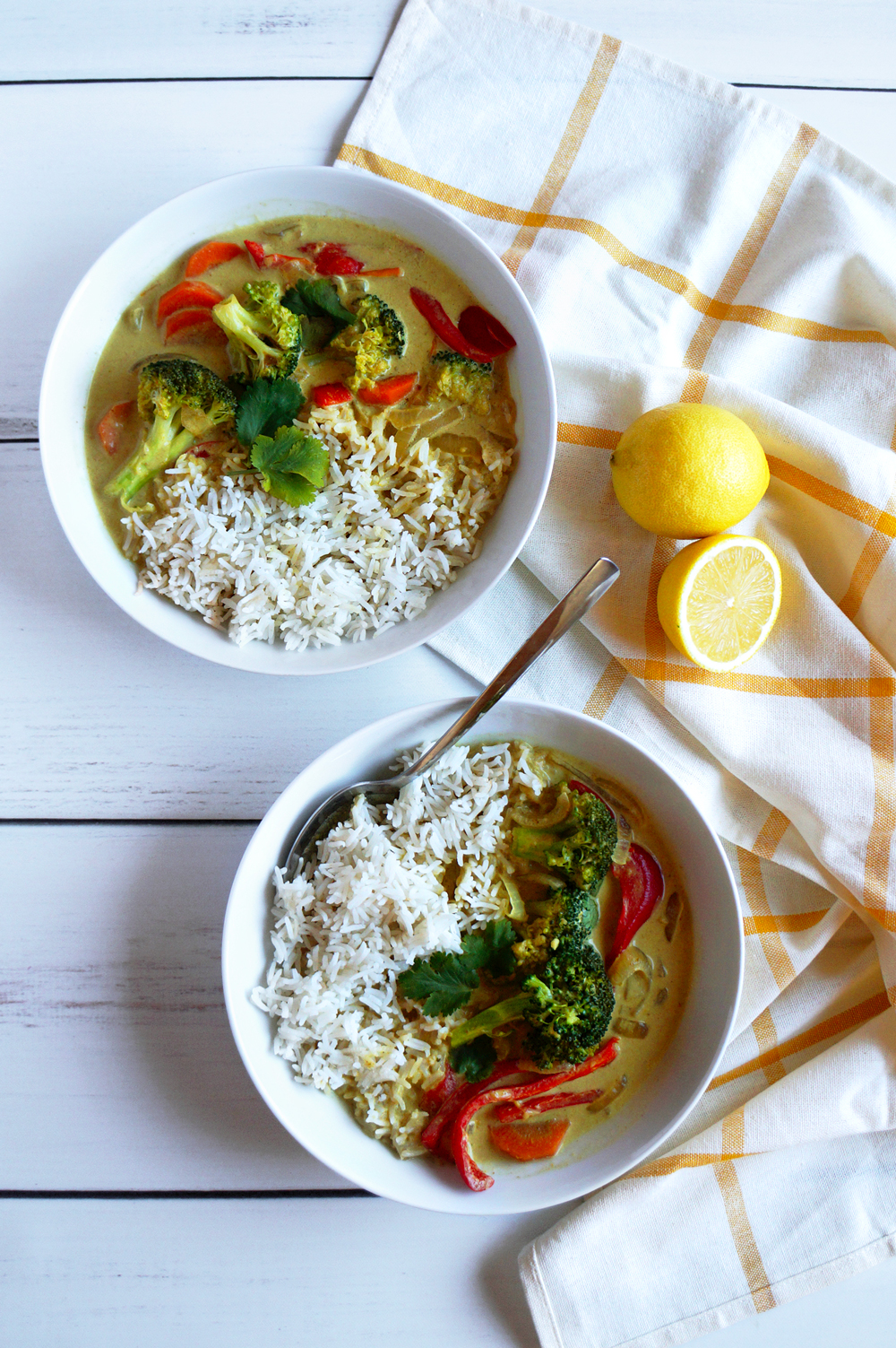 Two bowls of coconut curry on a white wooden table, with a white and orange striped tea towel and lemons.