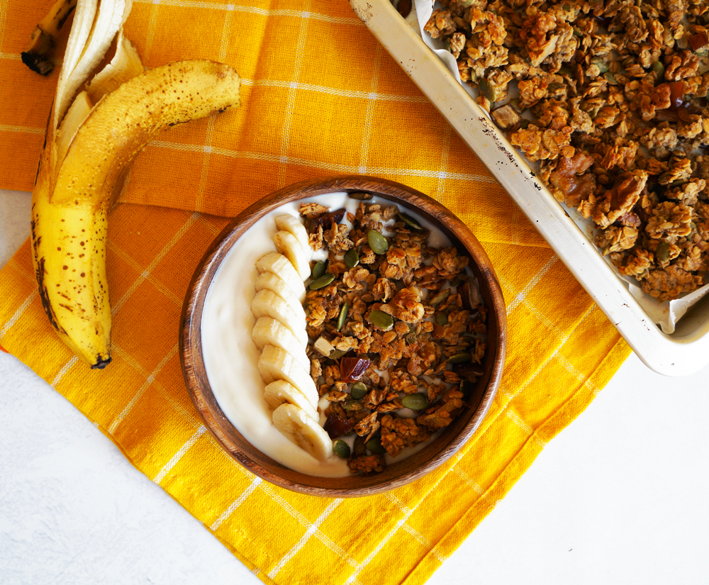 Banana bread granola in a wooden bowl with vegan yogurt and sliced bananas. With a baking tray of banana bread granola and a half peeled banana on top of a yellow tea towel.
