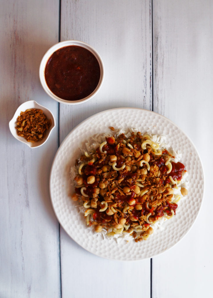 Koshari on a large white plate, vinegar tomato sauce, and crispy onions.