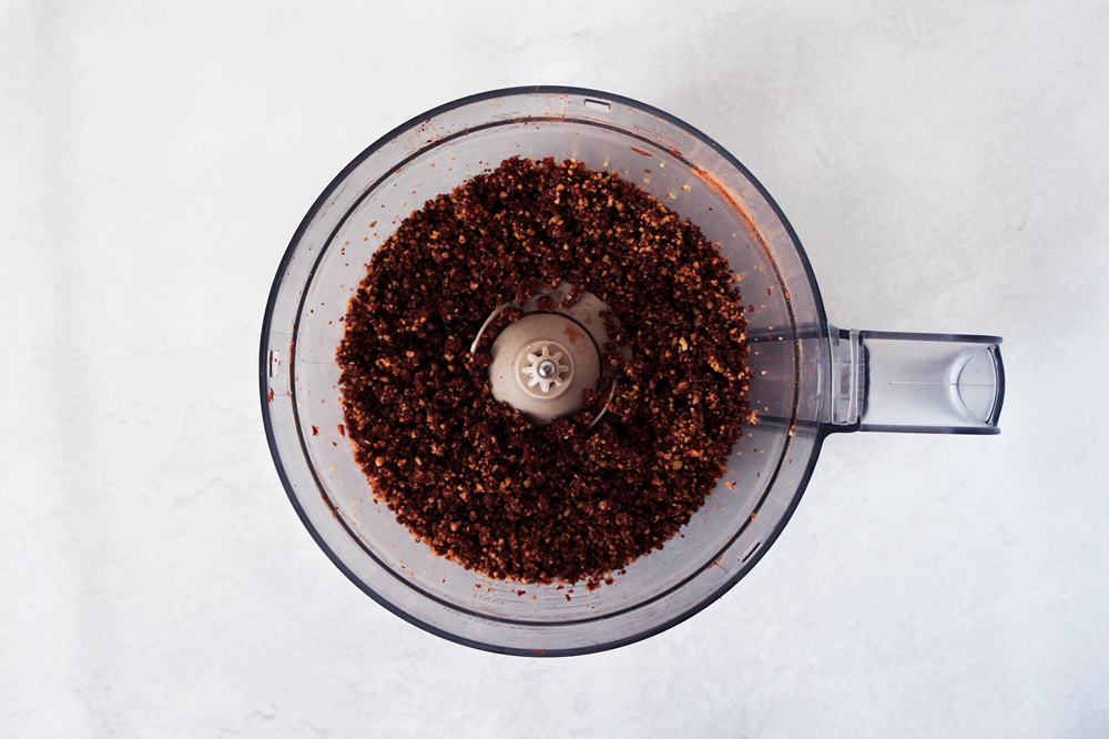 Crumbly mixture of walnuts, dates, and cacao powder in a food processor.