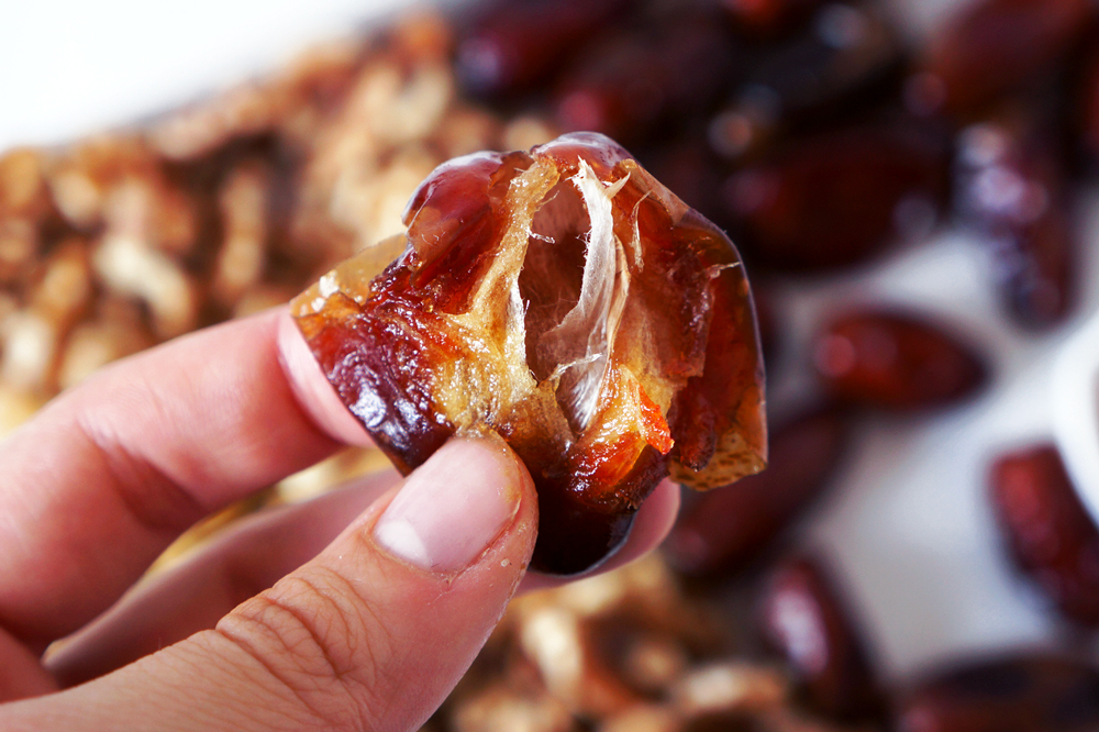 Hand holding a gooey, soft pitted date