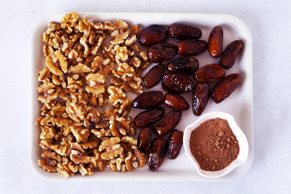 Walnuts, dates, cacao powder on a white tray