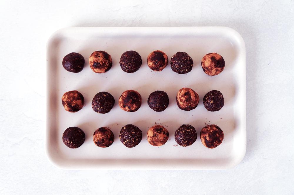 Walnut chocolate bliss balls arranged on a white tray
