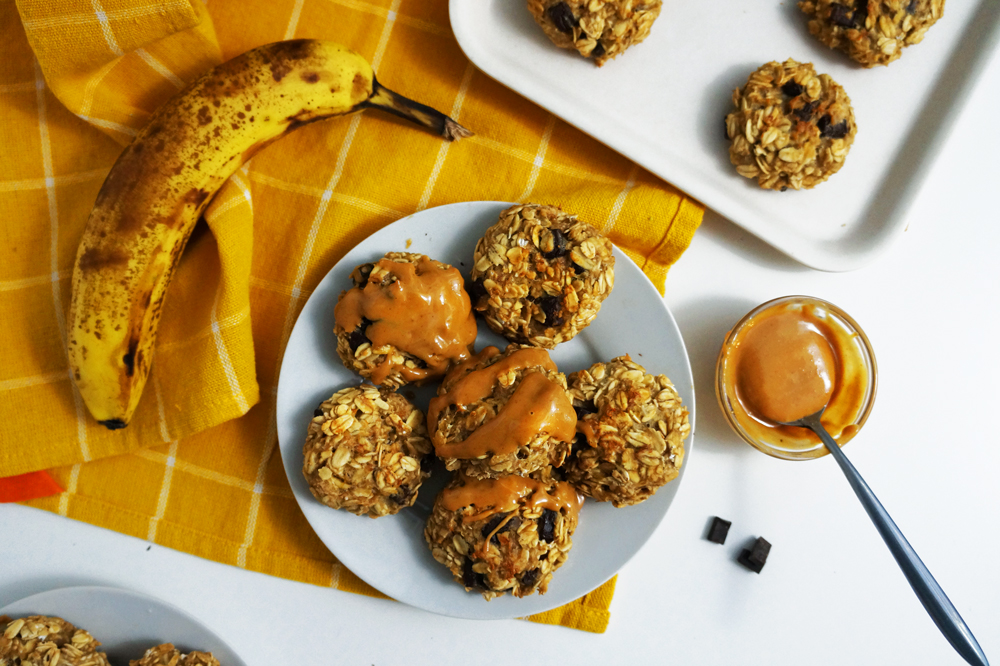 Vegan banana peanut butter chocolate oat breakfast cookies on a small white plate