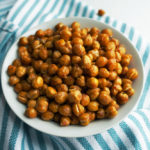Crispy chickpeas in a small white bowl on a blue and white striped towel.