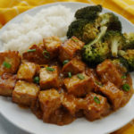 Vegan orange tofu on a plate with broccoli and rice