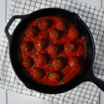Vegan high-protein textured vegetable protein (TVP) meatballs in a cast iron skillet full of tomato sauce and topped with chopped parsley.