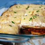 Tray of vegan moussaka with one slice cut out, exposing the layers of potato, lentils, eggplant, and creamy bechamel.
