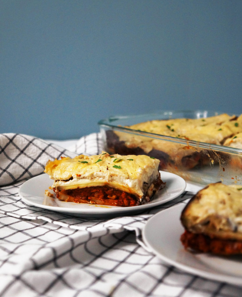 A slice of vegan moussaka with creamy bechamel sauce sprinkled with parsley on a small white plate.