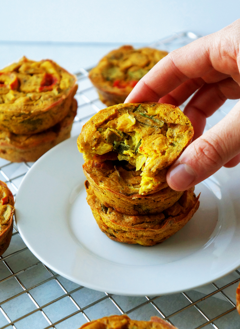 High-protein mini vegan frittatas  (egg muffins) made of chickpea flour and tofu stacked on top of each other with a bite taken out of the top muffin.