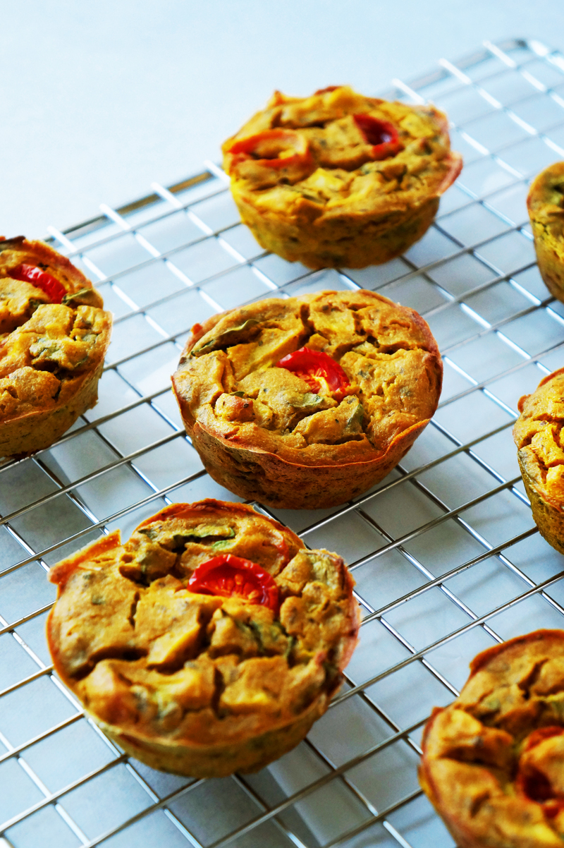 High-protein mini vegan frittatas  (egg muffins) made of chickpea flour and tofu on a cooling rack.