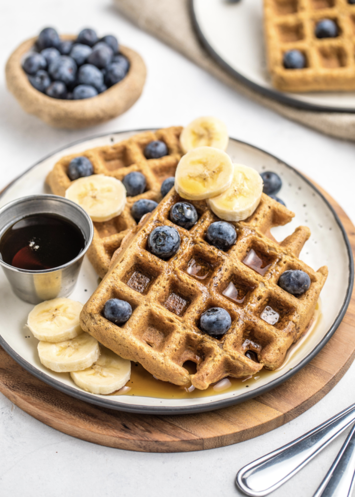 A great vegan pantry recipe – Vegan blender waffles on a plate topped with bananas, blueberries, and a side of maple syrup.