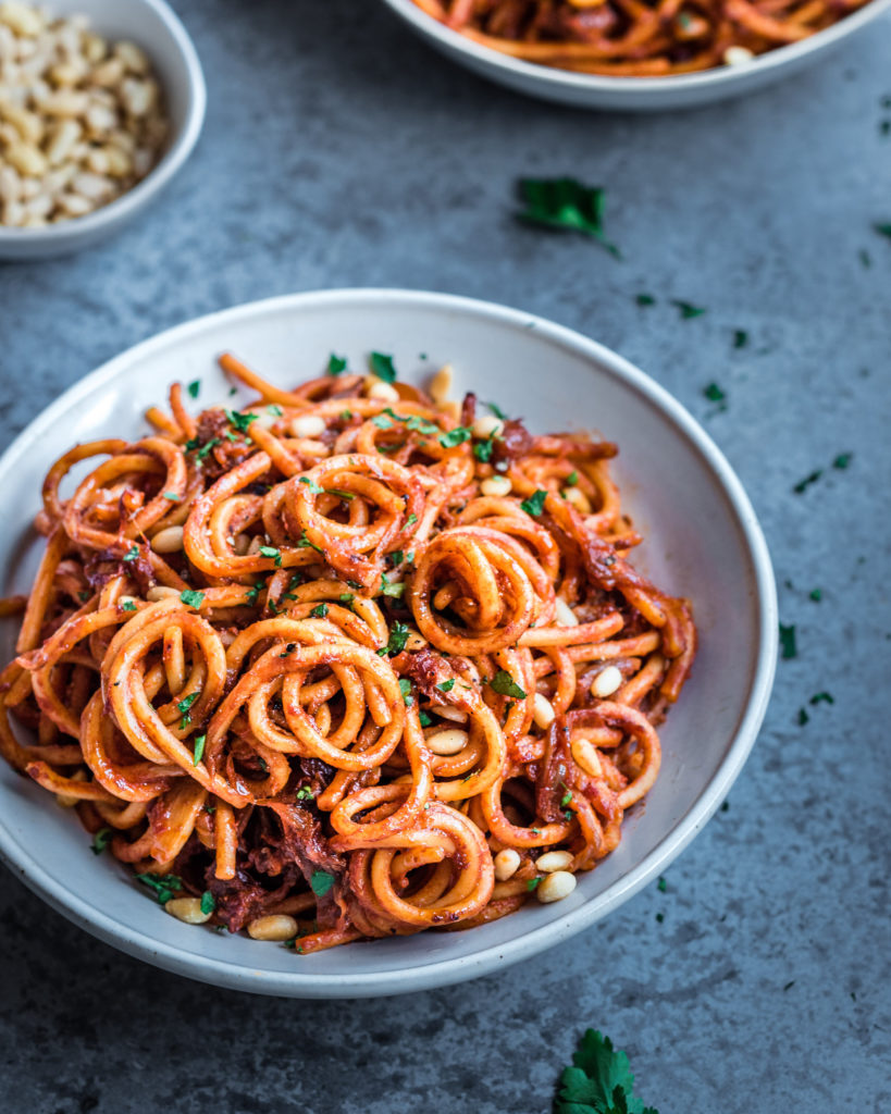 A great vegan pantry recipe – Vegan caramelized onion pasta in a white bowl.