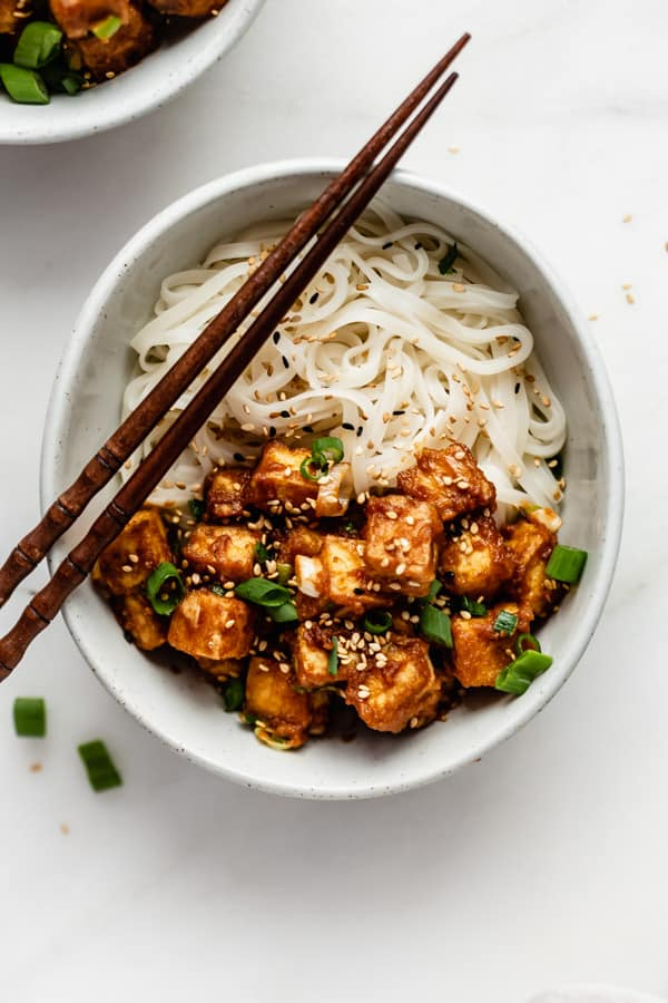 A great vegan pantry recipe – Peanut butter tofu in a small white bowl with rice noodles and chopsticks.