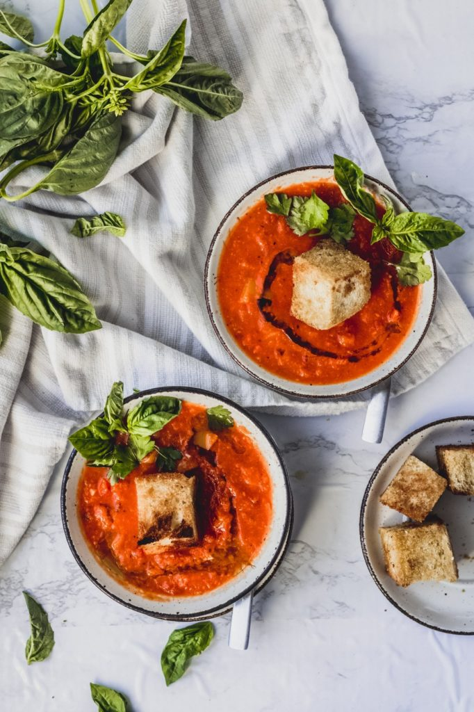 A great vegan pantry recipe – Vegan tomato soup with giant cheesy croutons in small bowls with a lot of fresh basil.