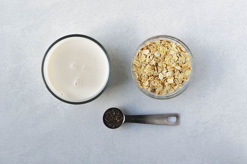 A cup of almond milk, a bowl of old-fashioned rolled oats, and a spoon of chia seeds.