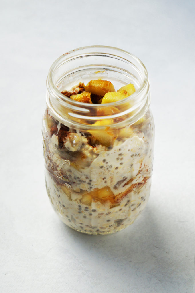 Jar of apple pie oats, topped with cooked diced granny smith apples and sprinkled with cinnamon