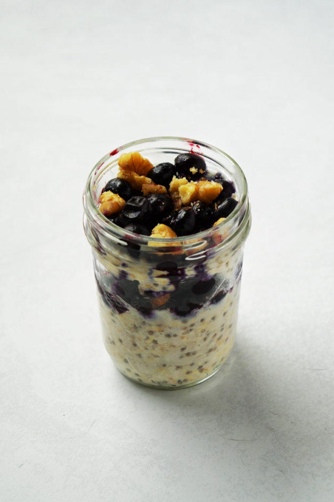Jar of blueberry muffin oats, topped with blueberries and chopped walnuts.