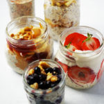 Jars of overnight oats on a white table.