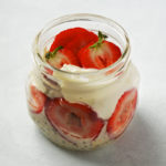 Jar of strawberries and cream oats, topped with sliced strawberries and vegan yogurt.