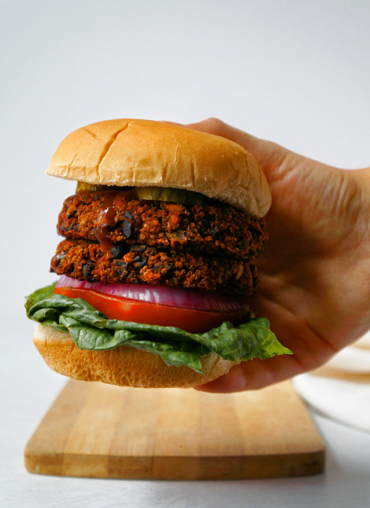 Double stacked BBQ black bean veggie burger with tomatoes, onions, lettuce, and pickles.