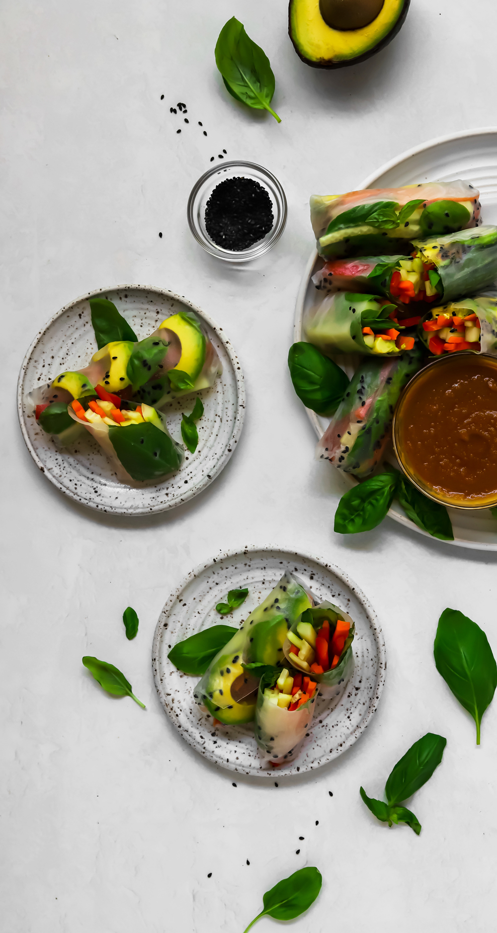 Basil summer rolls cut in half on small white speckled plates with a small bowl of black sesame seeds.
