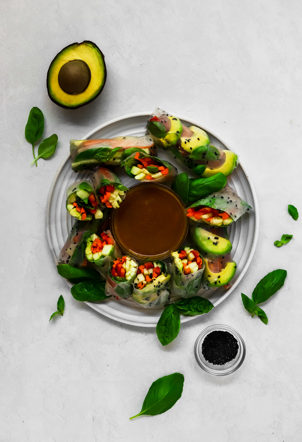Vegan basil summer rolls and peanut sauce on a large white plate.
