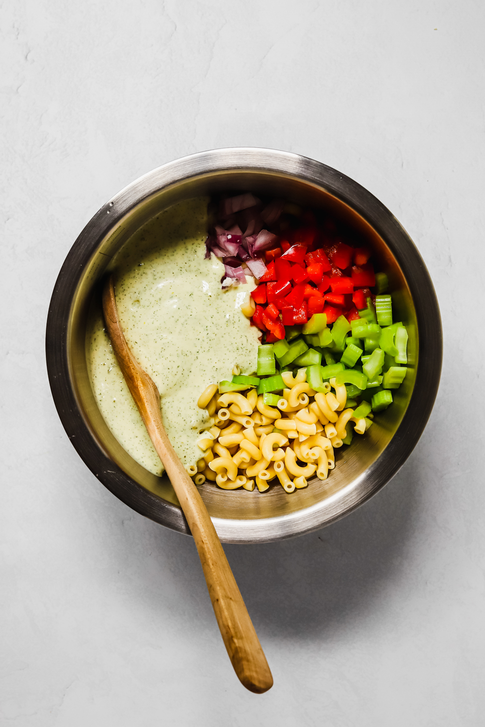 Elbow noodles, celery, red bell pepper, red onions, and mac salad sauce in a metal bowl with a wooden spoon.