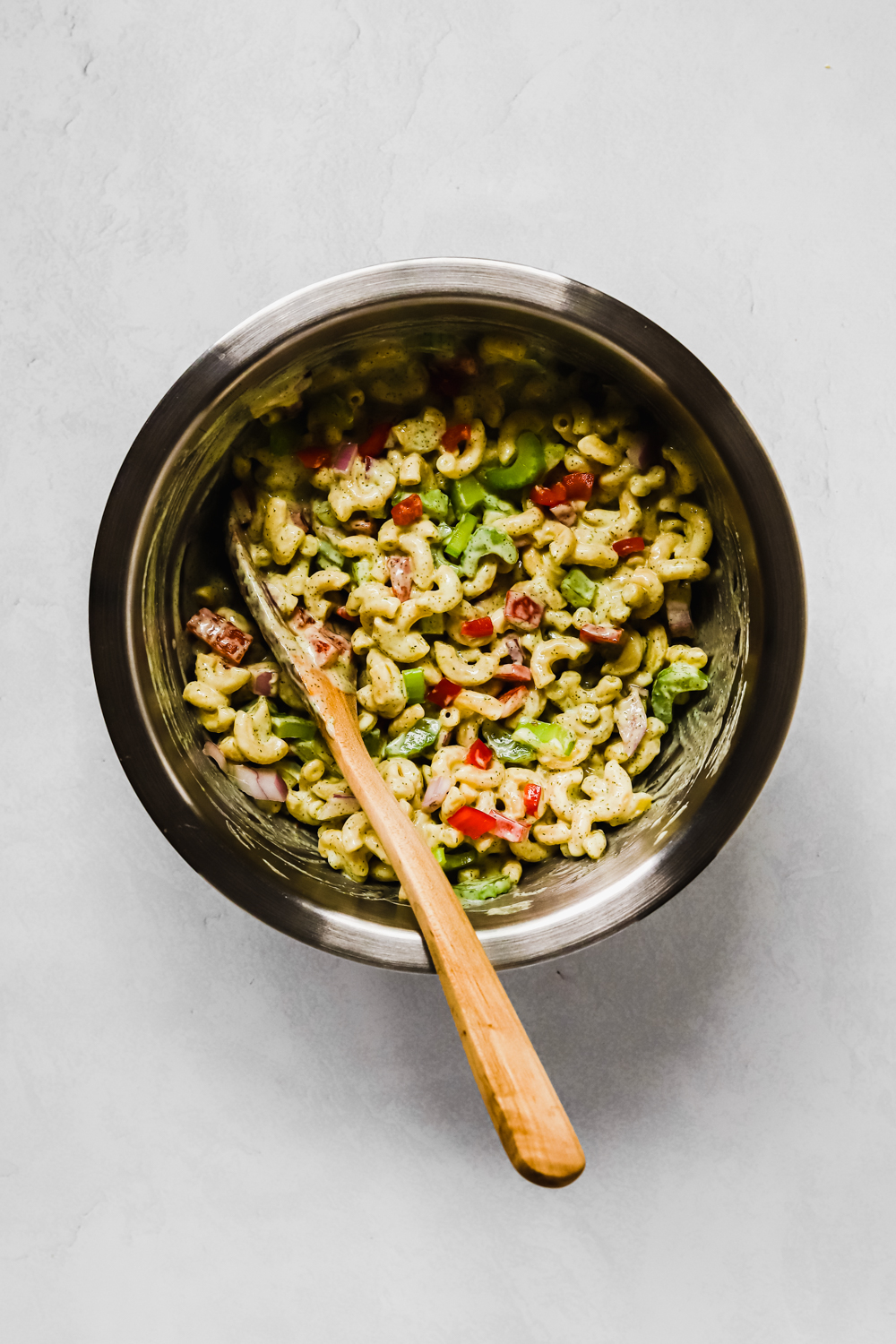 A metal mixing bowl of elbow noodles, chopped veggies, and mac salad sauce stirred together with a wooden spoon.