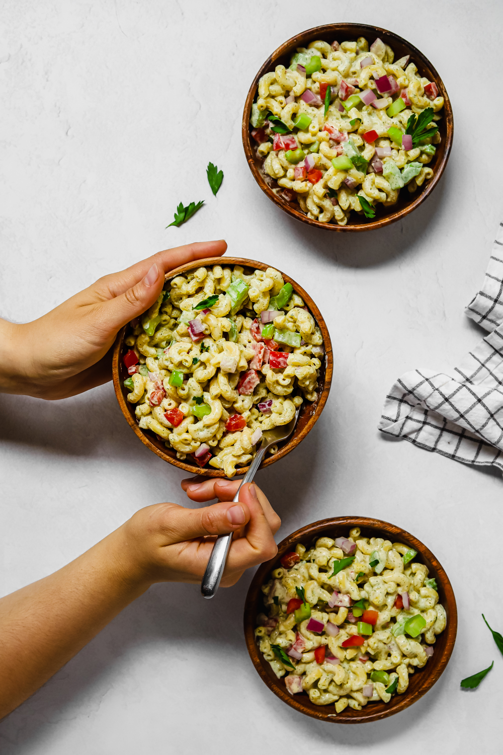 3 servings of vegan macaroni salad in small wooden bowls.