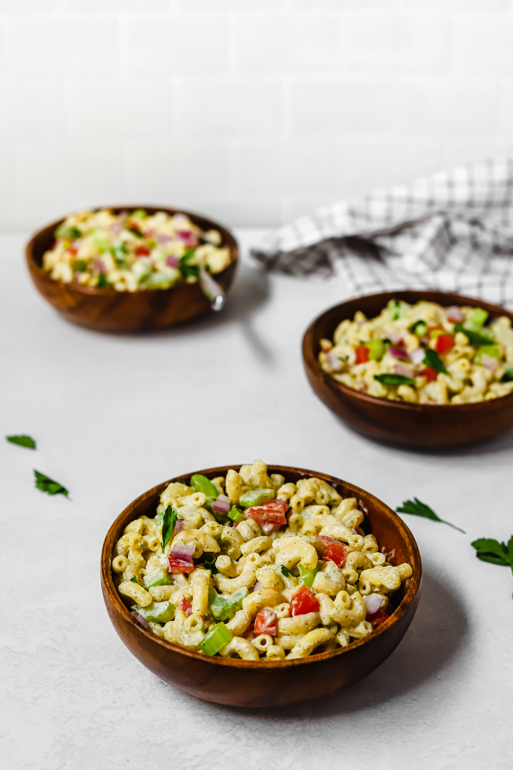 Healthy vegan macaroni salad in a small wooden bowl.