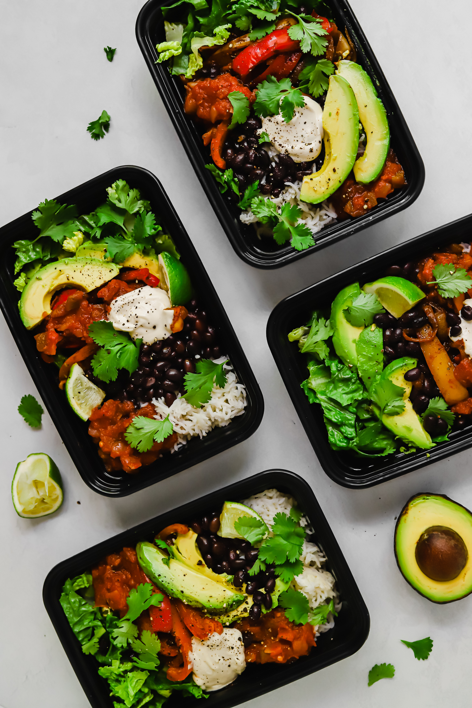 Meal prepped vegan burrito bowls in black plastic containers.